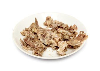 picked chicken bones on plate with white background