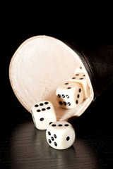 dice on old wood black table near a container