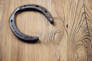 Old rusty horseshoe, wooden background, copy space