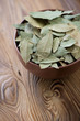 Bowl with dried bay leaves on a wooden table