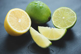Still life of sliced lemons and limes over black wooden surface