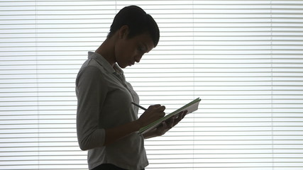 African American Business woman taking notes in office