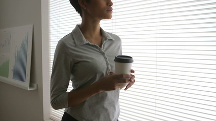 African American business woman drinking coffee and looking out