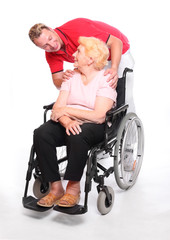 Elderly paraplegic woman in a wheelchair and her male nurse.
