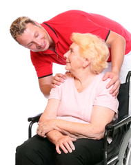 Elderly paraplegic woman in a wheelchair and her male nurse.