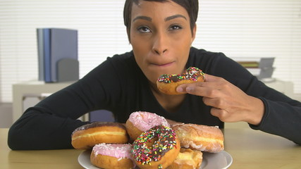 African American business woman eating a pile of donuts