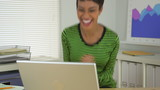 Smiling black business woman celebrating in office