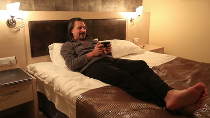 attractive man playing smart phone in hotel room