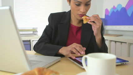 African American business woman eating croissant and using table