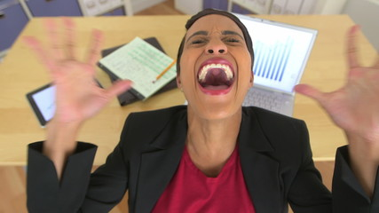 Close up of extremely angry business woman shouting in office