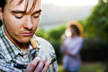 farmer sniffing wine cork to test the quality of the wine