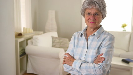 Happy old woman standing in living room