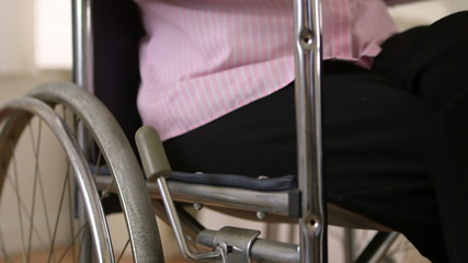 Mature woman using smartphone in wheelchair
