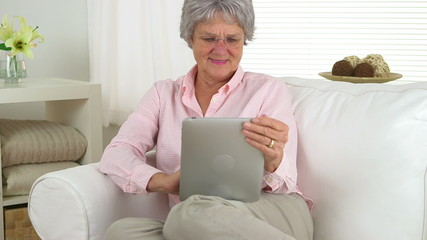 Happy senior woman using tablet