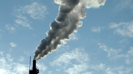 industrial smoke from chimney on blue sky with clouds