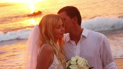 Newly married couple on tropical beach after sunset wedding