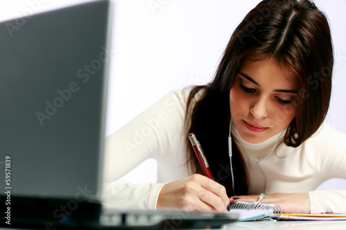 Young thoughtful student doing her homework