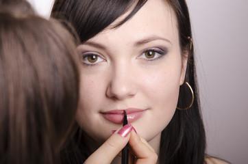 Визажист красит губы модели