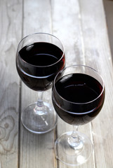 Two glasses of red white on the wooden background