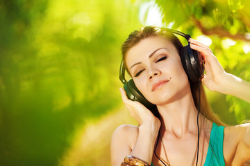 Beautiful young woman listen to music wearing headphones outdoor