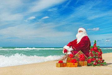 Santa Claus at sea beach with many gifts and decorated christmas