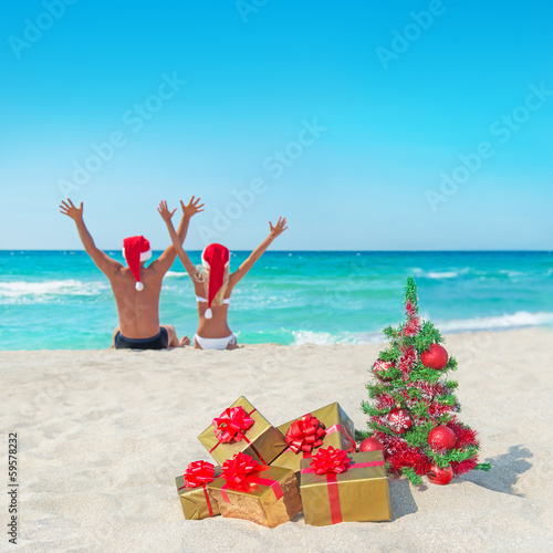 happy couple in santa hats at sea beach near christmas tree