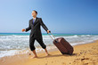 Young businessman in suit walking on a beach with his luggage