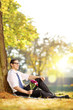 Handsome guy with flowers sitting on a grass and relaxing