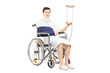 Smiling male patient with broken arm in a wheelchair with crutch