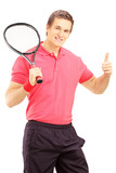 Young smiling man holding a tennis racket and giving thumb up