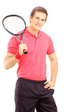 Young smiling man holding a tennis racket and posing