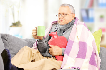 Ill man on a sofa covered with blanket drinking hot tea at home
