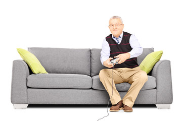 Senior man sitting on a couch and playing video games