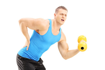 Young male athlete with back pain lifting a dumbbell