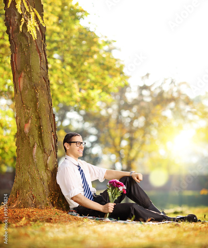 Handsome guy with a bunch of flowers in a park  on a sun