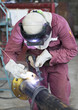Man in a safety suit is welding a metal pipe