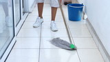 A young woman mopping the floor