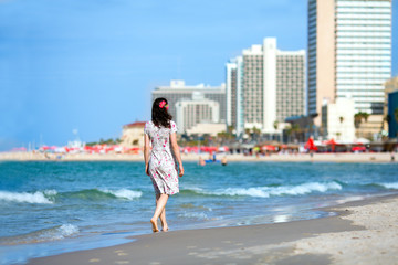 Young woman walking on the beach in Tel-Aviv