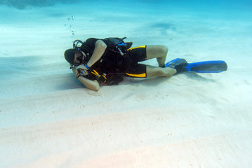 Diver Sleeping on Sandy Sea Bottom