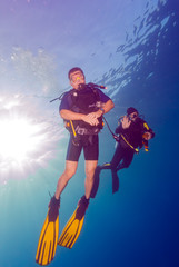 Two Scuba Divers with Sun Disc Behind