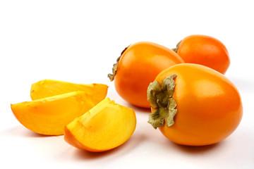 Whole and sliced kaki fruits on white background.