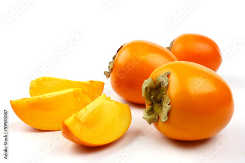 Whole and sliced kaki fruits on white background.