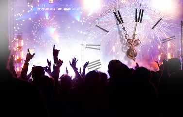 Clock close to midnight, fireworks and crowd waiting for New yea