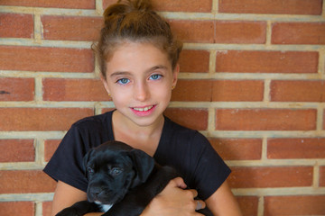 kid girl playing with puppy dog smiling