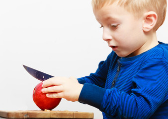 Boy child kid preschooler with knife cutting fruit apple at home