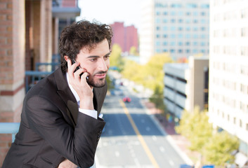 Businessman talking on phone, on a balcony of his apartment