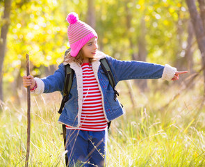 Hiking kid girl with backpack pointing finger in autum forest