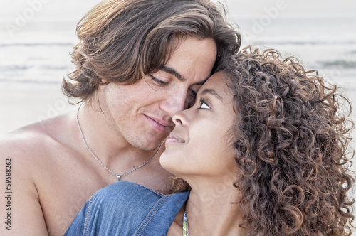 Young happy couple together at beach
