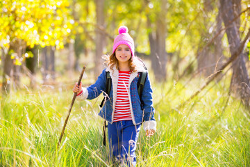 Hiking kid girl with backpack in autum poplar forest