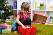 Little girl with present box near Christmas tree in room